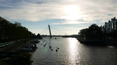 City canal panorama, boats moored along shore, cable stayed bridge on background Stock Footage