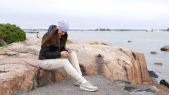 Cheerful young woman texting while sit at big stone, windy autumn weather Stock Footage