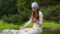 Young woman sit at park, look at smartphone and around, half length portrait Stock Footage