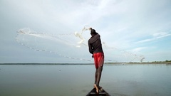 An African fisherman casts a wide net on his canoe with skill. About fishing Stock Footage