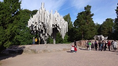 Tourists walk around ground square against Sibelius Monument, green park Stock Footage