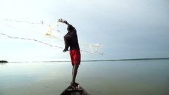 An African fisherman casts with skill a wide net on his canoe . About fishing Stock Footage