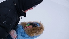 Guy plays with baby in winter park. Throw in the snow Stock Footage