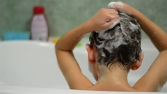 One boy who wash the head with shampoo in the bathroom at home 02 Stock Footage