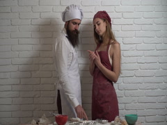 Date on the home kitchen. Young couple preparing food together with flour. Arkistovideo