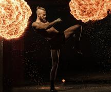 Professional fighter shadowboxing with fire and sparks on background Stock Photos