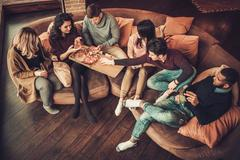 Group of multi ethnic young friends eating pizza in home interior Stock Photos