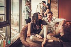 Group of multi ethnic young friends having fun in home interior Stock Photos