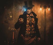 Steampunk man with pocket watch on vintage steampunk background Stock Photos
