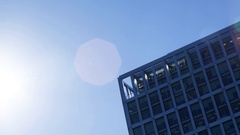 The sun disappearing behind a modern office block Stock Footage