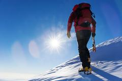 Extreme winter sports: climber at the top of a snowy peak in the Alps. Stock Photos