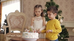 Small children cut a Christmas cake Stock Footage