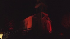 Spooky white church at night with red lighting Stock Footage