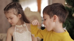Little brother and sister eating cake in the spacious living room on the Stock Footage