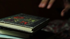 The hand opens the book, in dark Stock Footage