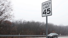 Speed Limit Sign 45 Miles Per Hour on road with passing traffic Stock Footage