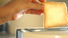 Woman's hand putting two pieces of bread in toaster machine Stock Footage