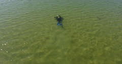 Aerial view of diver in full gear swims in shallow water in sea 4k Stock Footage