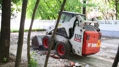 Wheel forklift truck rakes construction debris in the street Stock Footage