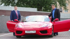 Two men sit in a Ferrari red car on the street in summer Stock Footage