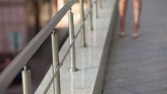 Legs of a young woman walking down the street next to a metal fence Stock Footage