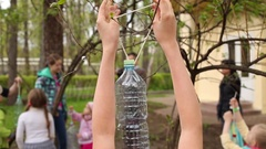 The girl hangs the bird feeder made from a plastic bottle Stock Footage