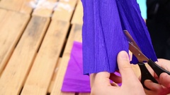 Girl cuts a circle of blue corrugated paper sitting at the table Stock Footage