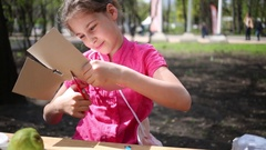 Girl cuts cardboard sitting at the table in the park Stock Footage
