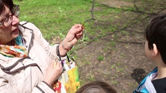 Biologist Marina Kostina showing bud on tree for children fingering leaves Stock Footage