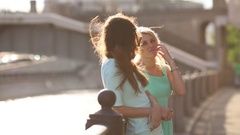 Two girls standing on the street and talking at a sunset Stock Footage