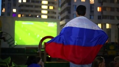 A man stands with the Russian flag on the shoulders and cheer Stock Footage