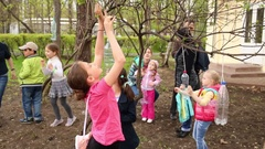 Children hangs a bird feeder made from a plastic bottle Stock Footage