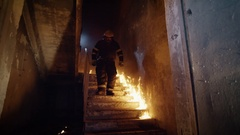Fully Equipped Firefighter Runs Down on Burning Stairs. Building on Fire. Stock Footage