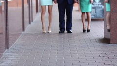 A man walks with two girls on the street, only legs visible Stock Footage