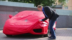 A man takes out cover from a red Ferrari car on the street Stock Footage