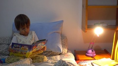 Child looks in to a book in the bed Stock Footage