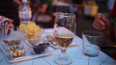 Person pours beer into a glass on the table with nuts in a cafe Stock Footage