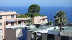 Green trees and bushes on the flat roofs of the city against the sea Stock Footage