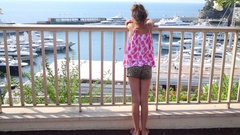 Girl is standing at the fence and looking at the yachts in the port at sunn.. Stock Footage
