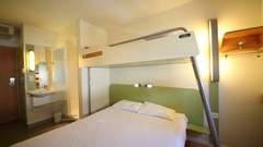 Hotel room with a double bed with a top bunk and shower in a hotel ibis bud.. Stock Footage
