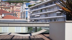 Curve bench on the roof of the building in a big city in the mountains Stock Footage