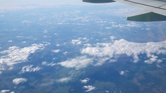 Earth, white clouds and aircraft wing, view from a plane window Stock Footage