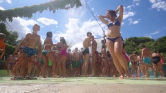 Woman and lots of people having fun in jets of fountain Stock Footage