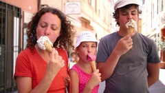 Mother with two children eating ice cream on the walk Stock Footage