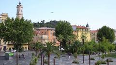 Plane flies over the buildings near the Esplanade de la Bourgada in Nice, F.. Stock Footage