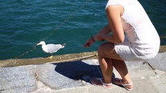 Woman in a white dress feeds a seagull on the concrete pier near the sea Stock Footage