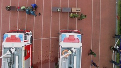Two firefighters teams work with hoses near fire-engines Stock Footage
