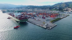 Tugboats work with vessel near container terminal Voltri Europa Stock Footage