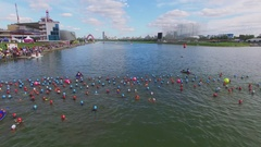 Lot of sportsmen in water wait for start of triathlon contest Stock Footage