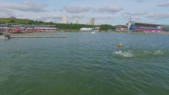 Spectators watch sportsmen finish swimming race and run to bicycle area Stock Footage